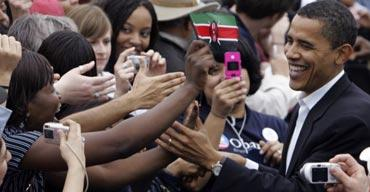 A woman holds a Kenyan flag as Barack Obama greets supporters in Austin, Texas. Photograph: LM Otero/AP